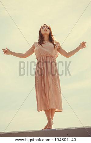Hobby idyllic aspects of femininity concept. Woman dancing on jetty without shoes wearing beautiful long light pink dress.