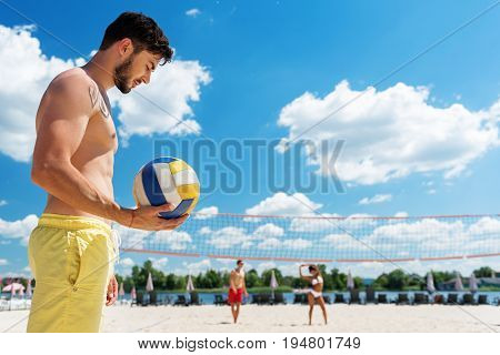 Profile of pensive young bearded man standing with his head low on beach playground and holding ball in one hand. He is playing volleyball on sand with his friends. Copy space in right side