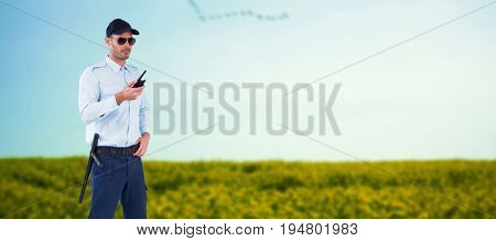 Security officer in uniform holding walkie talkie against flock of bird flying over field