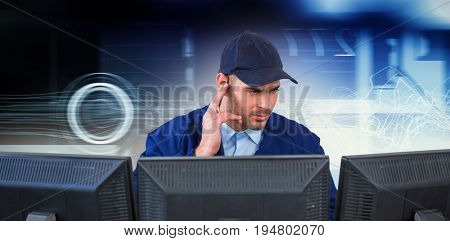 Security officer listening to earpiece while using computer at desk against virus background