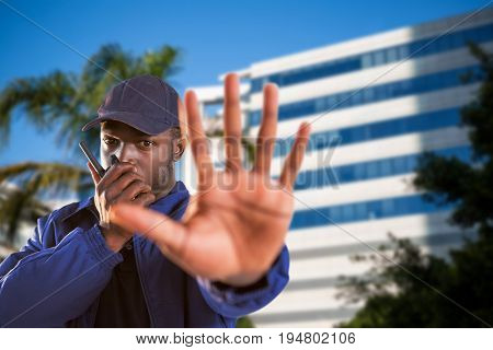 Portrait of confident security talking on walkie talkie and making stop gesture against tree by glass building