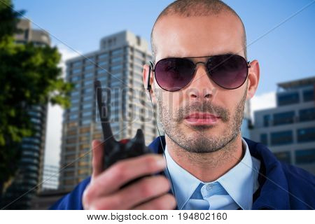 Portrait of security officer talking on walkie talkie against beautiful cityscape against clear sky