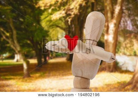 Wooden 3d figurine standing and holding a red heart in front against row of trees in park