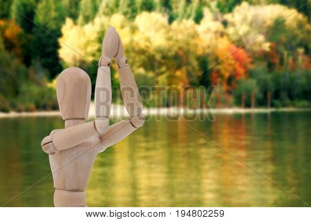 Wooden figurine standing with both the hands joined against river against autumn trees