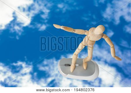 3d image of carefree wooden figurine standing on computer mouse against view of beautiful sky and clouds