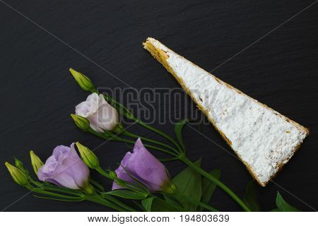 Classic French white praline layer cake decorate by violet flowers on black slate stone plate