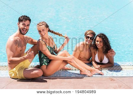 Portrait of two happy young couples relaxing in open air swimming pool. One pair is standing waist deep in water and hugging. Other one is sitting on edge of poolside. Everybody is smiling