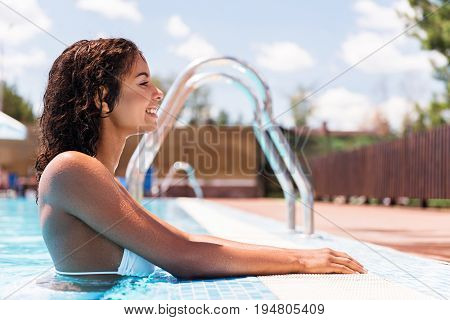 Profile of jolly young mulatto lady standing in water and holding by hands by pool edge. She is smiling and looking forward. Copy space in right side