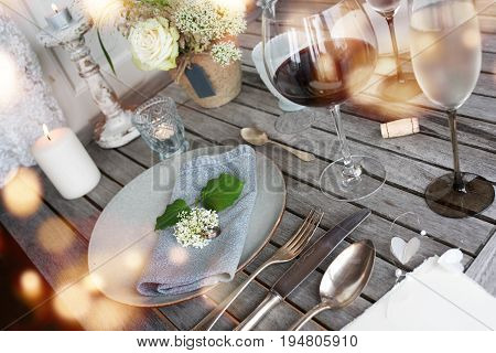 Table decoration in country house style on a rustic wooden table mit bokeh for a festive dinner