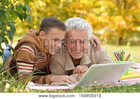 portrait of  boy and  grandfather with a laptop in park