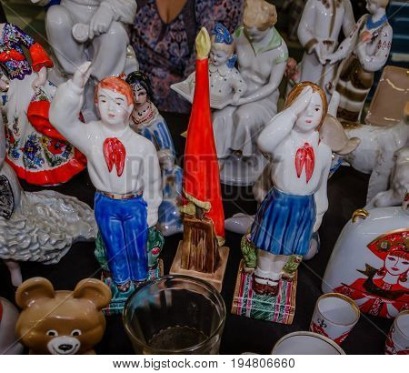 Moscow, Russia - March 19, 2017: Vintage porcelain figurines of scouts, a boy and a girl saluting at the red flag of pioneers. Objects of the era of the USSR are popular with collectors and foreigners
