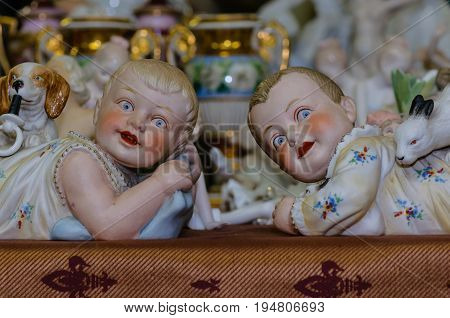 Moscow, Russia - March 19, 2017: Rare vintage collection porcelain figurines of ruddy boys and girls of the Victorian era with a rabbit and a dog on the counter of an antique store