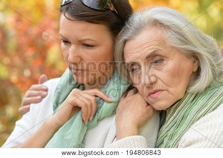 Portrait of a senior woman with daughterin autumnal park