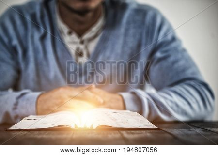 Bright spot of a flare against man with bible praying on table