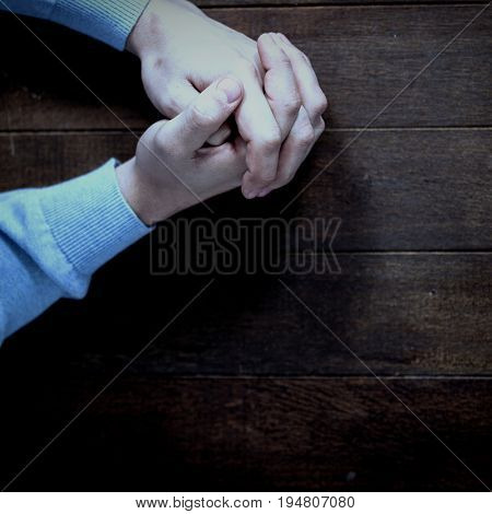 Cropped hands of man praying on wooden table