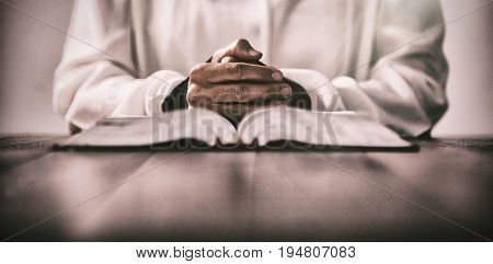 Mid section of woman sitting at desk with bible against gray background