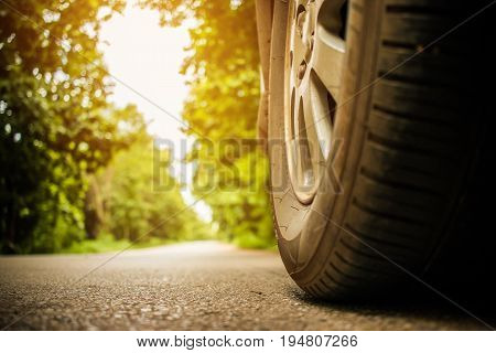 old wheel of cars on asphalt road on summer day in countryside green forest nature street