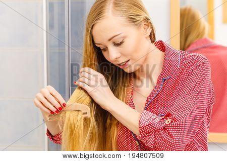 Woman Combing Her Long Hair In Bathroom
