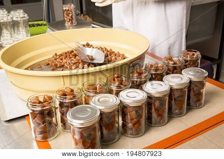 Artisanal production of caramel toffee sweets butterscotch candies. Woman with white gloves shaking put in jar get in the jugs the pieces of butterscotch candies traditional sweets of France