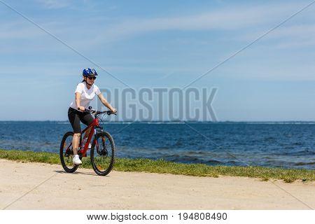 Woman cycling at seaside