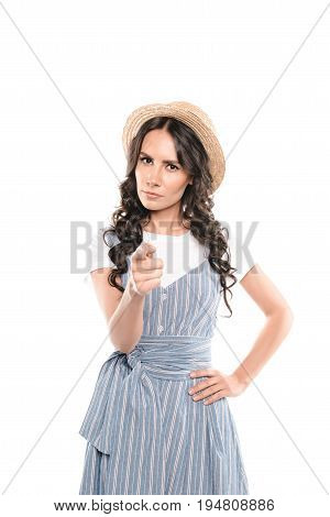 Serious young woman in straw hat pointing at camera isolated on white