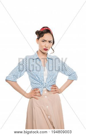 Serious Young Asian Woman Standing With Hands On Waist And Looking At Camera Isolated On White