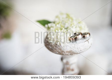 Still life with wedding rings on an old white candle holder in shabby chic style