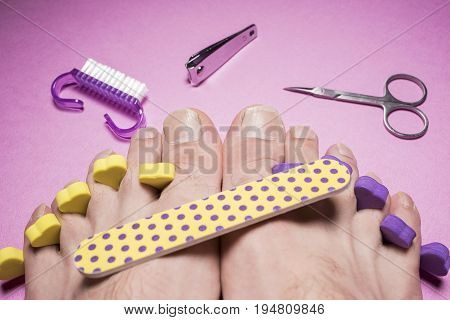 Male pedicure, nail file,  scissors on a pink background