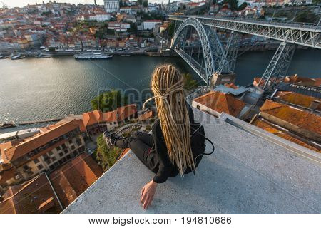 Beautiful woman with dreadlocks on the viewing platform opposite the Dom Luis I bridge across the Douro river in Porto, Portugal.