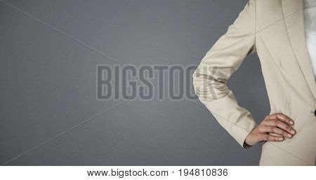 Mid section of businesswoman with hand on hip against grey background