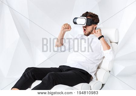 Excited young man is getting experience using VR-headset glasses of virtual reality gesticulating with his hands. A young man sits on a comfortable armchair in a room with white walls