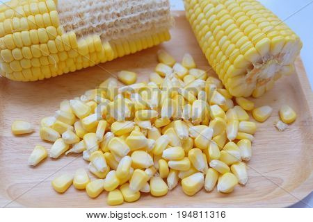 Closeup fresh sweet corn pods and corn kernels on wooden background.