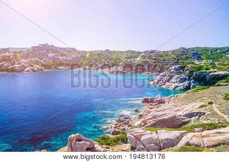 Bizarre granite rock and azure bay with sun flares in Capo Testa, Sardinia, Italy.