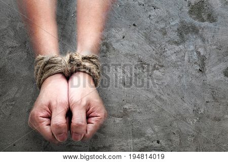 victim slave prosoner male hands tied by big rope in the concrete background. Concept image of people who addicted or slaved some bad thing.