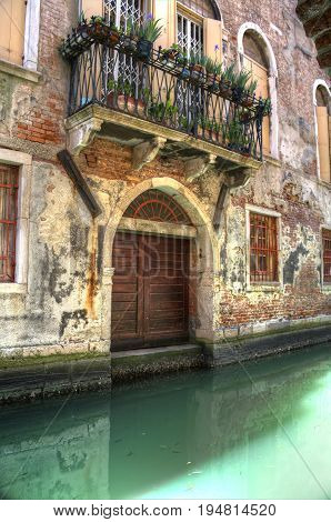 A High Dynamic Range image of a door in Venice Italy with a canal.