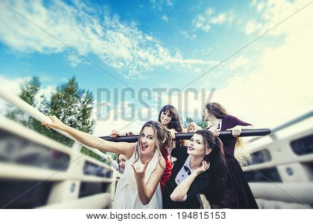 Young beautiful happy women celebrate bachelorette party in a convertible limousine