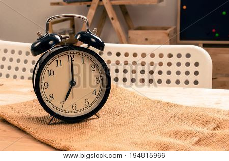 black vintage retro alarm clock times at 7 o'clock morning on wooden table selective focus copy space vintage color tone working morning time concept