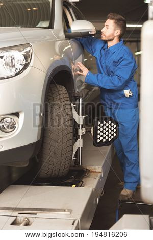 Thorough checkup. Fine able diligent mechanic performing a general checkup on the car and employing special tool and regulating tires