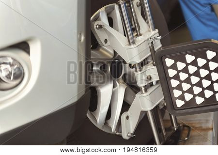 Best tools in industry. Local professional known servicemen using professional equipment for regulating wheels of a car and checking their quality