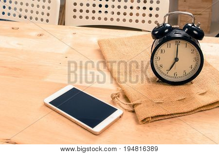 smartphone and black vintage retro alarm clock times at 7 o'clock morning on wooden desk in room selective focus copy space vintage color tone technology and working morning time concept