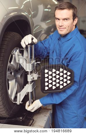 Best tinker in town. Handsome trustworthy excellent serviceman employing special equipment for doing a checkup on quality of the tires he installing