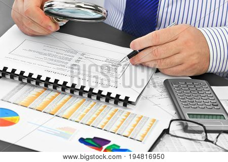 Businessman with pen and magnifying glass, analyzing  financial documents  in the office