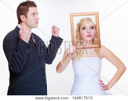 Wedding day negative relationship concept. Groom and bride holding posing with empty photo frame having bad argument.