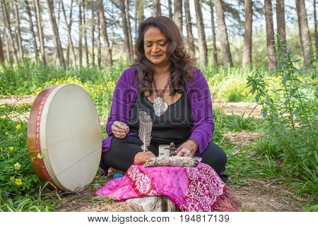Female shaman lighting candle at altar seated on the ground