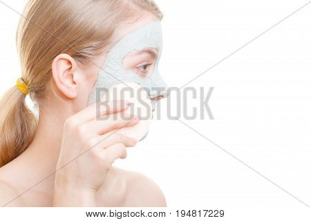 Skin care cosmetology concept. Woman removing mud algae mask from face with cosmetic sponge.