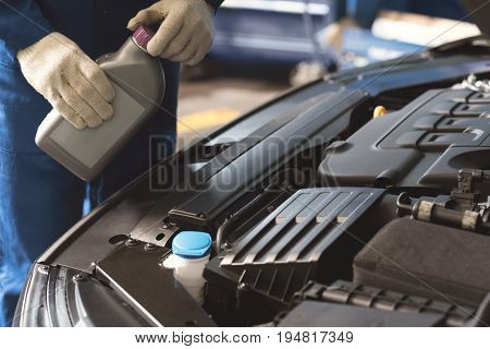 Professional care. Competent successful local tinker performing a maintenance procedure and using specific fluid for making the car working better