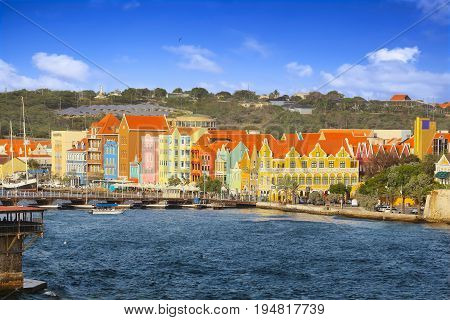 WILLEMSTAD, CURACAO - APRIL 18, 2017: Waterfront with colorful houses and seafront esplanade in Willemstad