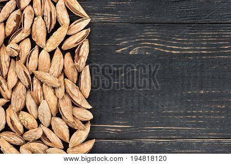 Scattered uzbek inshell almonds on an empty wooden background