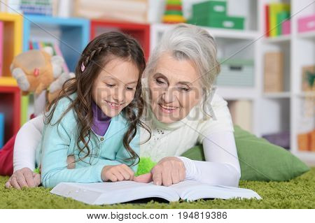 Grandmother reading book with her little granddaughter