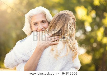 Sharing love with close people. Caring loving retired woman walking in the park while expressing delight and hugging mature daughter